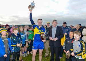 Colin Ryan of Newmarket lifts the Clare Champion Cup following the win over Inagh-Kilnamona in the Clare Champion Cup final at Clarecastle. To the right is Joe Cooney, vice Chairman of Clare GAA who made the presentation.