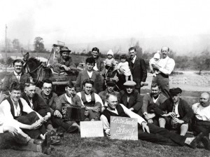 A group of German workers on the Shannon Scheme celebrate their imminent departure from Ireland with a session in the company of their Irish friends. The sign held by the man lying on the grass in the front, reads, Last Sunday in Ireland. Whit Sunday 1929.    With the permission of Patricia Haselbeck Flynn, copyright the Haselbeck Collection