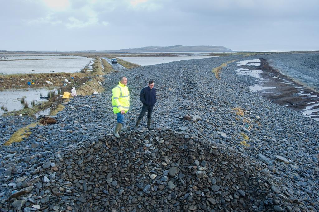 Farmers  Vincent Hedderman and Matthew Carmody of Rahona, Carrigaholt, examine the road between Rahona and Kilbaha where the sea covered the road. Photograph by John Kelly.