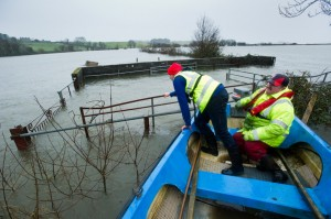 Gerry Murtagh and his son Damien  float by their submerged cattle crush yard with flood damage on over 20 acres of their farm at Lacknashannagh, Kildysart on the Shannon Estuary. Photograph by John Kelly.
