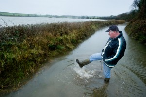 Local farmer Tom Finn at the entrance to his farm at Lacknashannagh, Kildysart on the Shannon Estuary, where he has 22 acres of grazing and meadow under severe flood. Photograph by John Kelly.