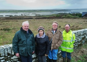 Representatives of three of the four families trapped by flooding, seen in the background, at Kilcredaun, Carrigaholt; From left; Jim and Bernie O Brien, Pat Gavin and Stephen Rowan. Photograph by John Kelly.