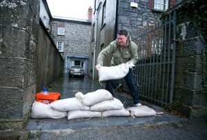Garrett Ahern lays sandbags at the entrance to his home in Thomond Villas, Clarecastle over the weeekend. Photograph by Arthur Ellis