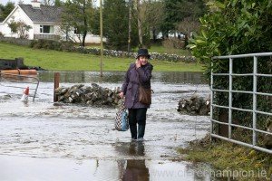Mary Collins makes her way home from shopping through flood water in Skehanagh near Ardrahan in South Galway. Photograph by Arthur Ellis.