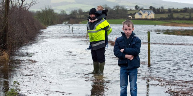 Rory Moloney with his eight-year-old twins, Caoimhe and Jack, at the completely submerged roadway to their home near O'Callaghans Mills. His wife and kids have had to leave the family home due to the flooding but Rory remains to look after his animals and farm.