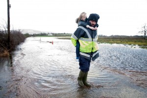 Rory Moloney with his eight-year-old daughter, Caoimhe at the completely submerged roadway to their home near O'Callaghan's Mills. Photograph by Arthur Ellis