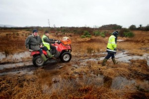 Ger Mulqueen (front) and James Pepper on the Quad with Rory Moloney walking alongside use the only means available to access their homes through dangerous bogland , the roadway to their homes near O'Callagha'ns Mills in Clare is completely submerged. Photograph by Arthur Ellis