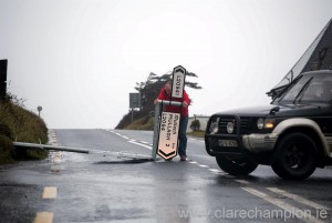 A motorist clears a fallen direction sign from a road in West Clare