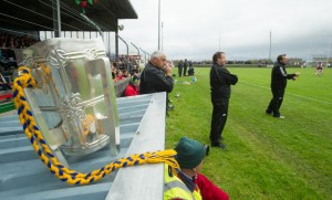 The Liam Mac Carthy Cup takes pride of place  in Pairc Naomh Mhuire, Quilty as Clare manager Davy Fitzgerald mans the sideline during the challenge game between Clare and Galway as part of the Kilmurry Ibrickane GAA Club 100th anniversary celebrations. Photograph by John Kelly.