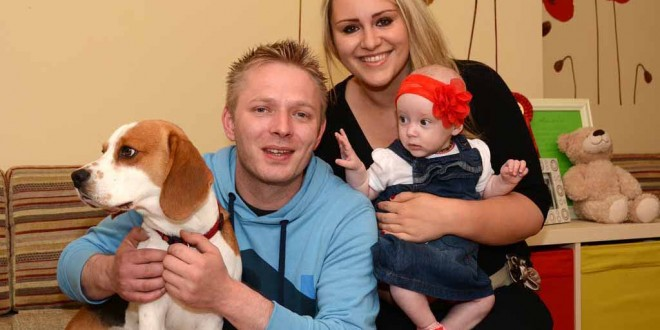 Daniel Drzewiecki and Julija Kolpakova at home with their baby daughter, Laura Olivia, and dog, Charlie.