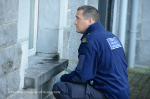 A Crime Scene Investigation Garda examines the scene around the broken window at Ennis Courthouse. Photograph by John Kelly