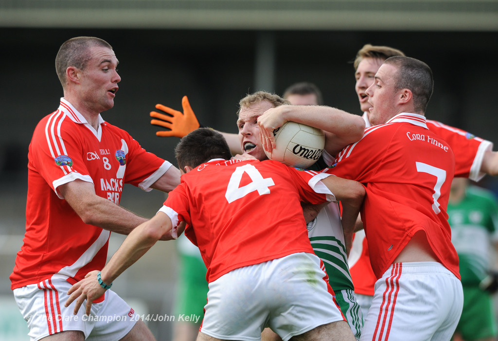 Wolfe Tones Ian Collins is well tackled by Corofin's John Keane, Shay Malone and Colm Rice during their Intermediate final at Cusack park. Photograph by John Kelly.