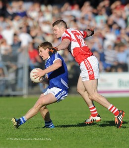 Podge Collins of Cratloe in action against Conor Brennan of Eire Og during their senior football final at Cusack park. Photograph by John Kelly.