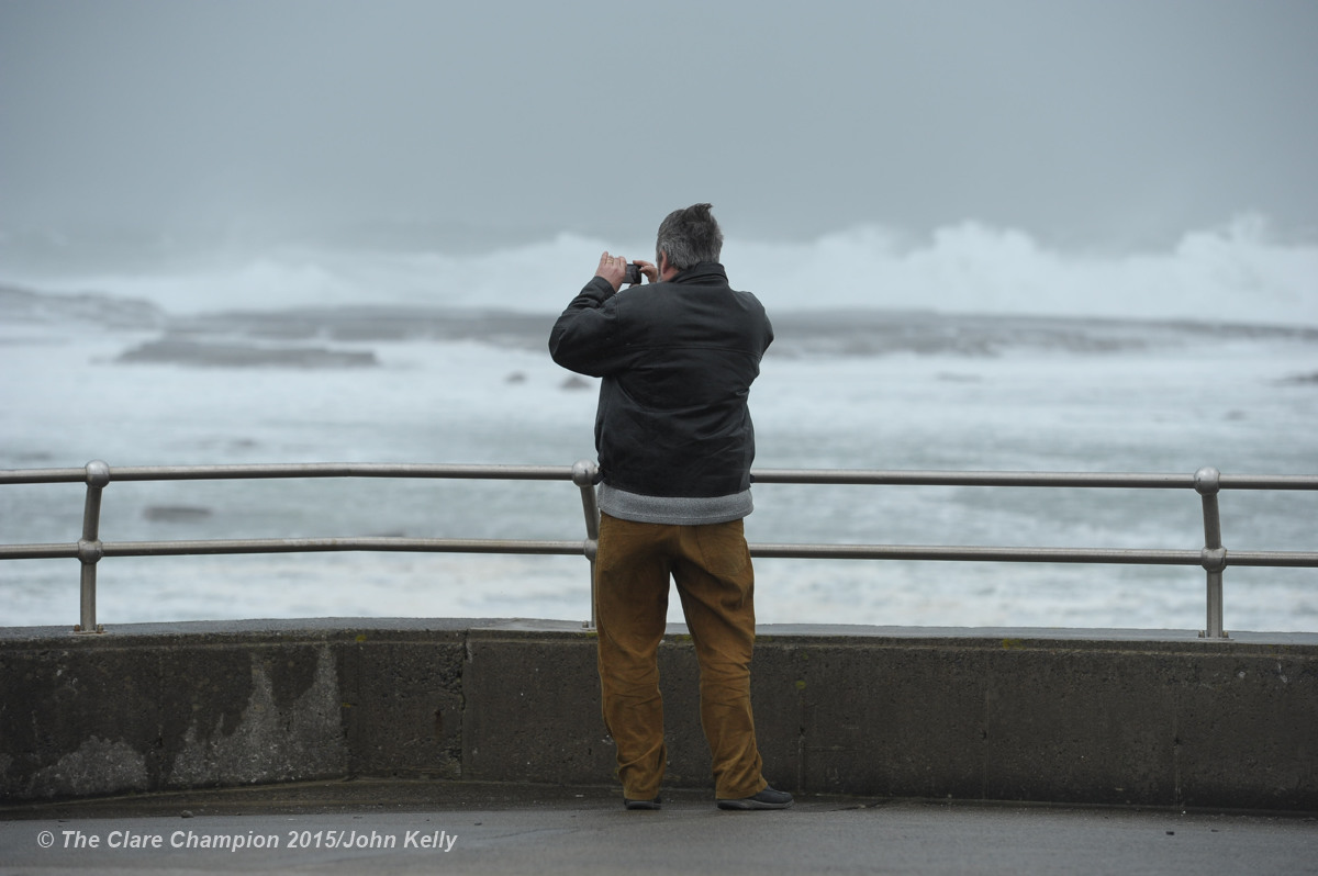 A man photographs the high seas and huge waves forming at The Pollack Holes, Kilkee as the wind picks up on Monday afternoon. Photograph by John Kelly.