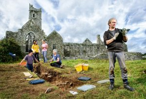 Archaeologist Graham Hull recording information uncovered on an archaeological dig in the shadow of Quin Abbey. In the background are volunteers Ritchie Jones, Ita Lawton, Fiona Clancy and Mary Howard. Photograph by John Kelly.